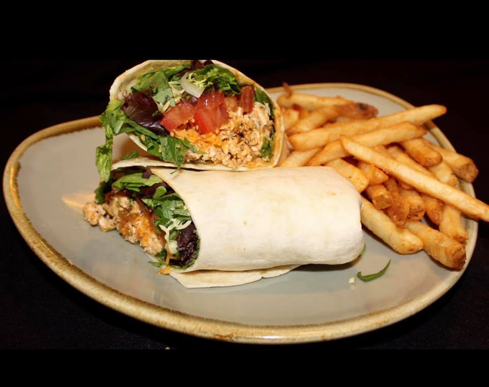 Buffalo chicken wrap with lettuce and tomato with French fries