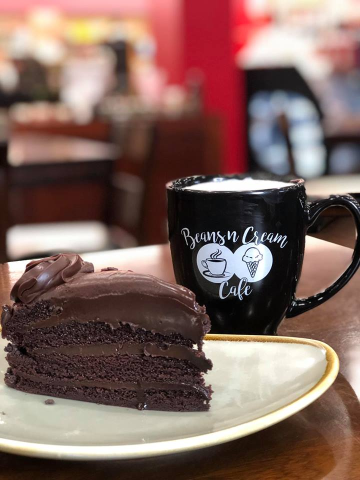 Slice of chocolate cake with a coffee mug