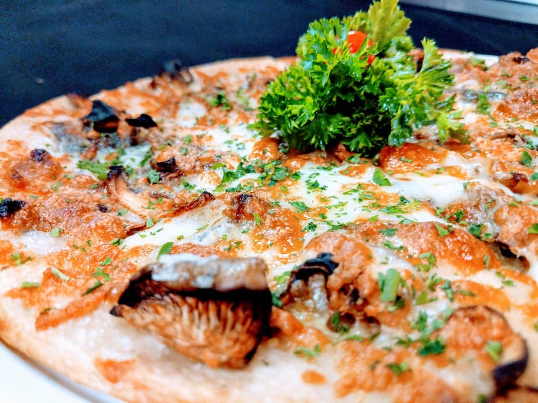 Asiago cream sauce with dried mushrooms, anchovies, mozzarella & parsley pizza