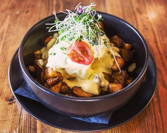 Potatoes topped with two farm fresh eggs, roasted root vegetables served with avocado hollandaise