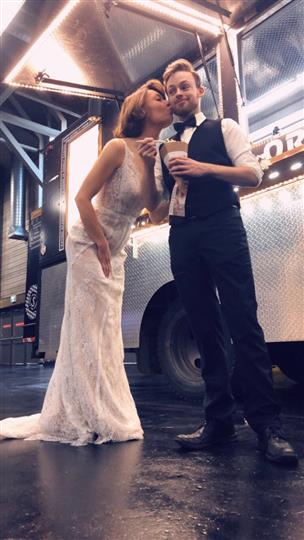 Bride and Groom posing for a picture infront of Food Truck holding a Spaghetti Cone