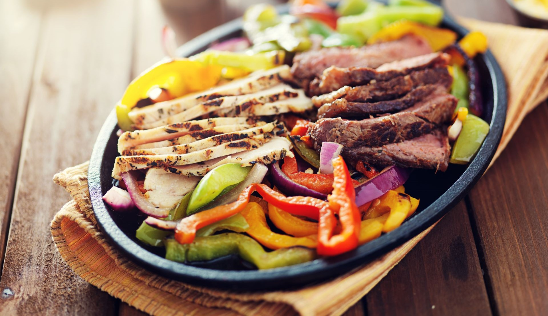 Fajitas with steak and chicken on rustic wooden table