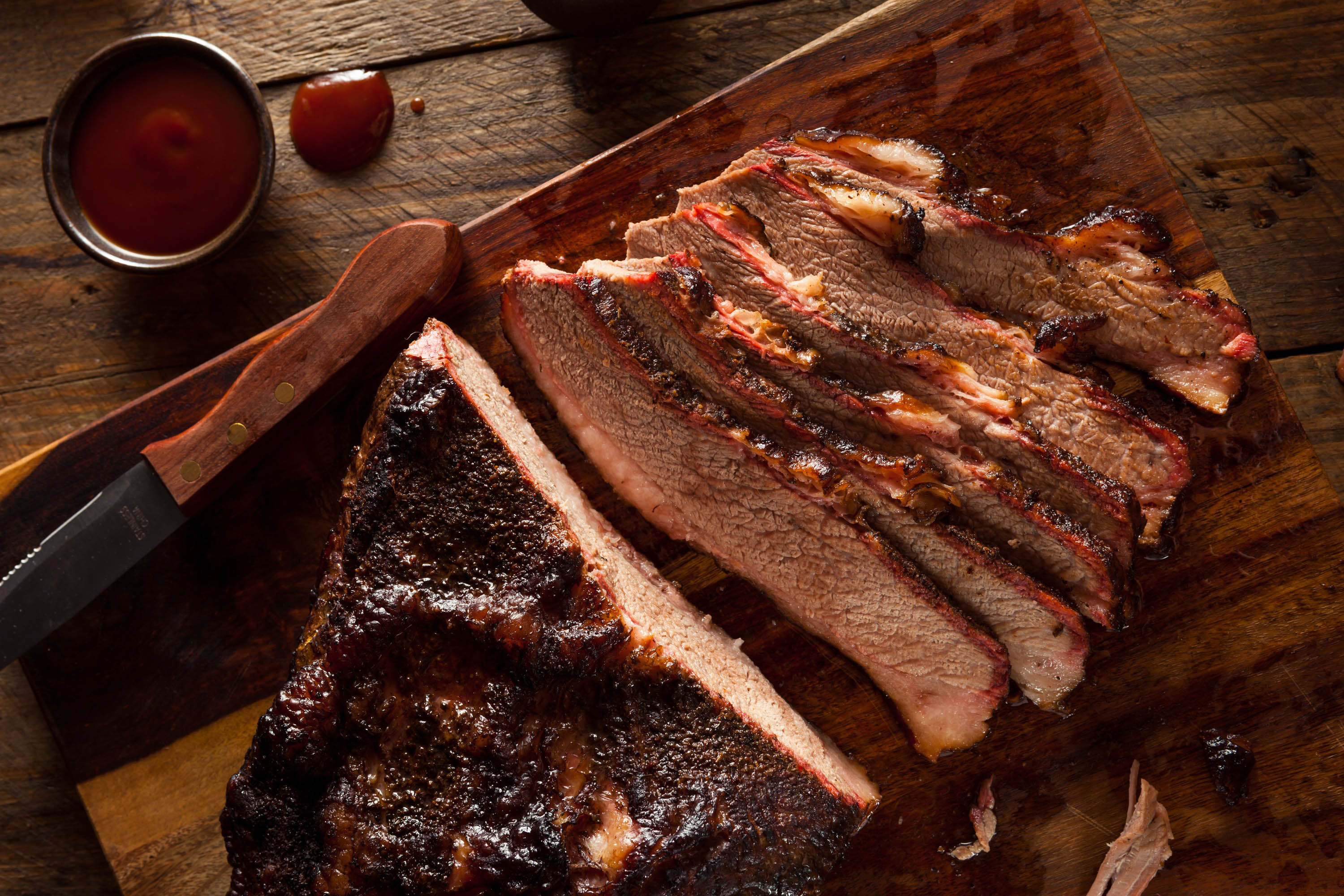 Sliced beef brisket on a wooden board with a small container of BBQ sauce
