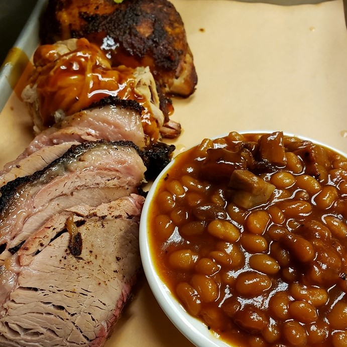 Smoked beef brisket, BBQ pulled pork and BBQ chicken on a tray with baked beans