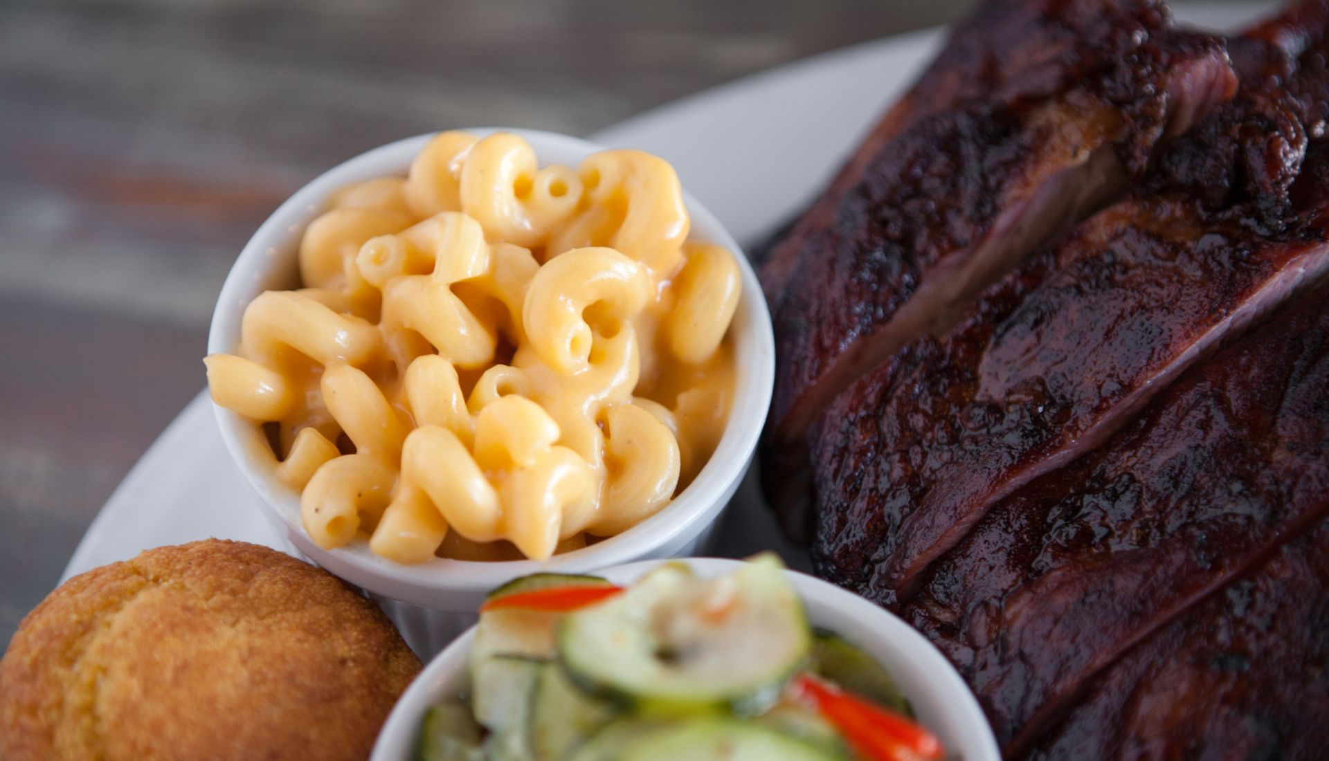 Mac and cheese in a small bowl next to corn bread, a rack of BBQ ribs and assorted pickled vegetables