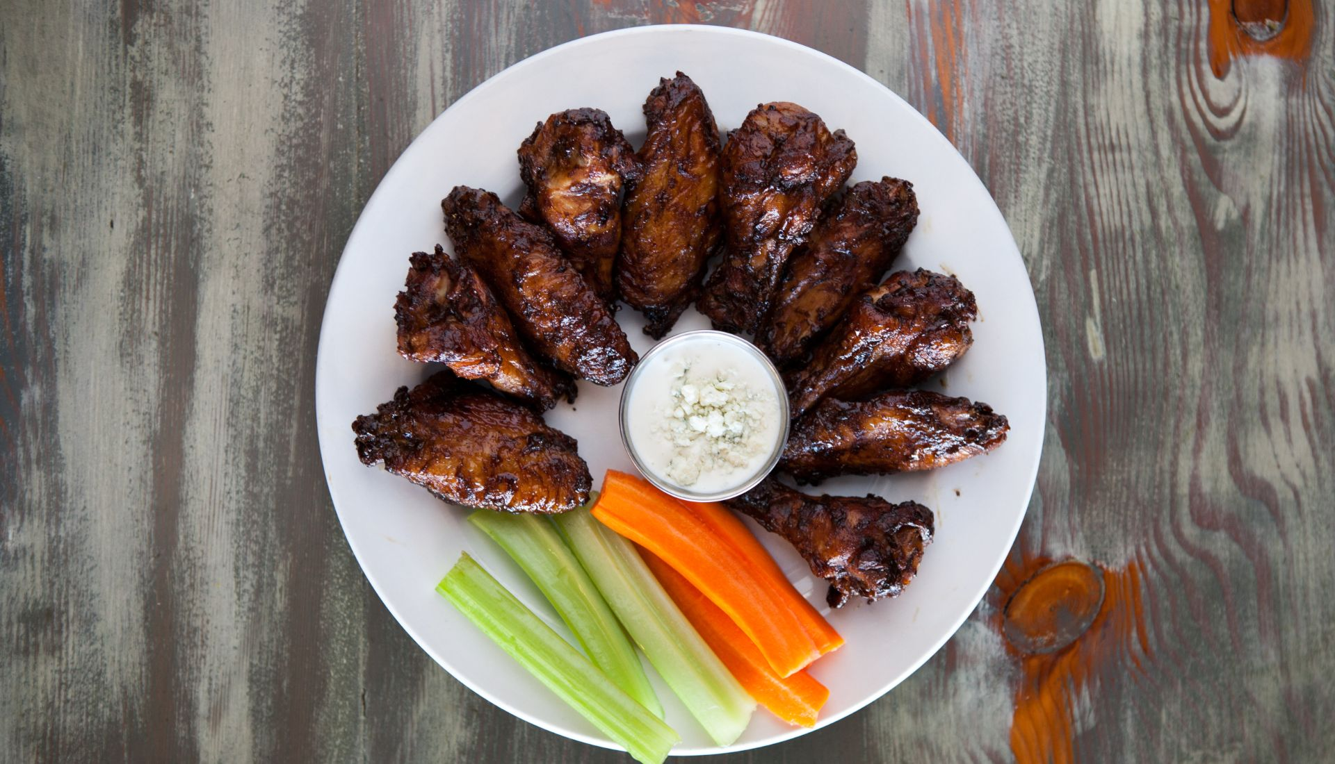 BBQ chicken wings on a plate with bleu cheese, carrots and celery