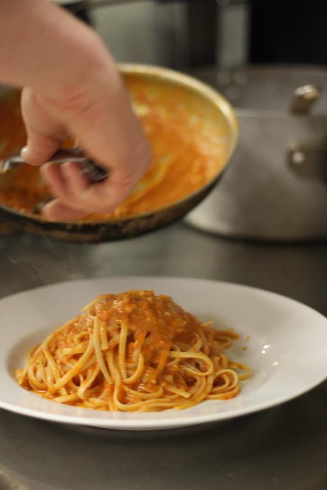 chef topping spaghetti with sauce in a plate