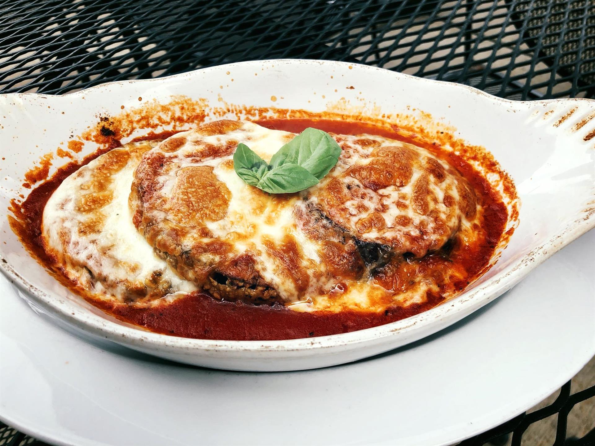 Eggplant Parmigiana covered in metled cheese and topped with sauce