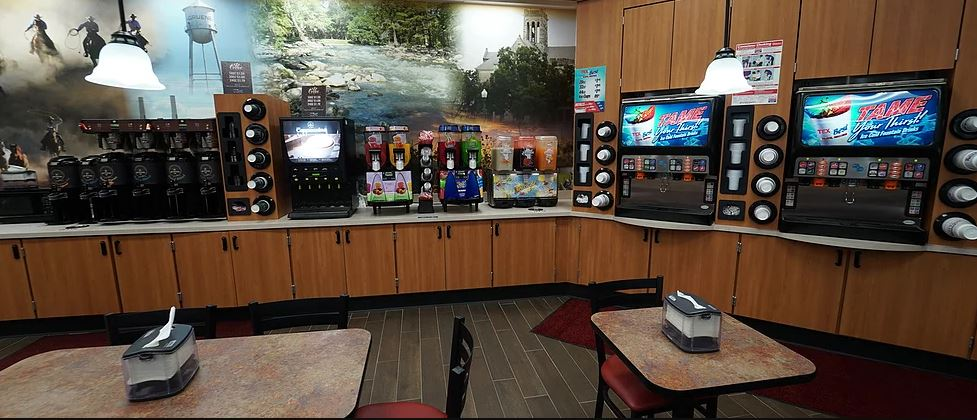 Interior dining area drinks section with a coffee machine and soda machine with cups on the side