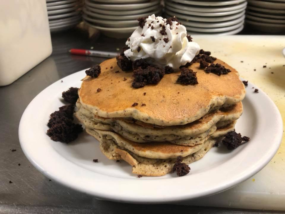 Stack of pancakes with whipped cream and topped with crumbled brownie