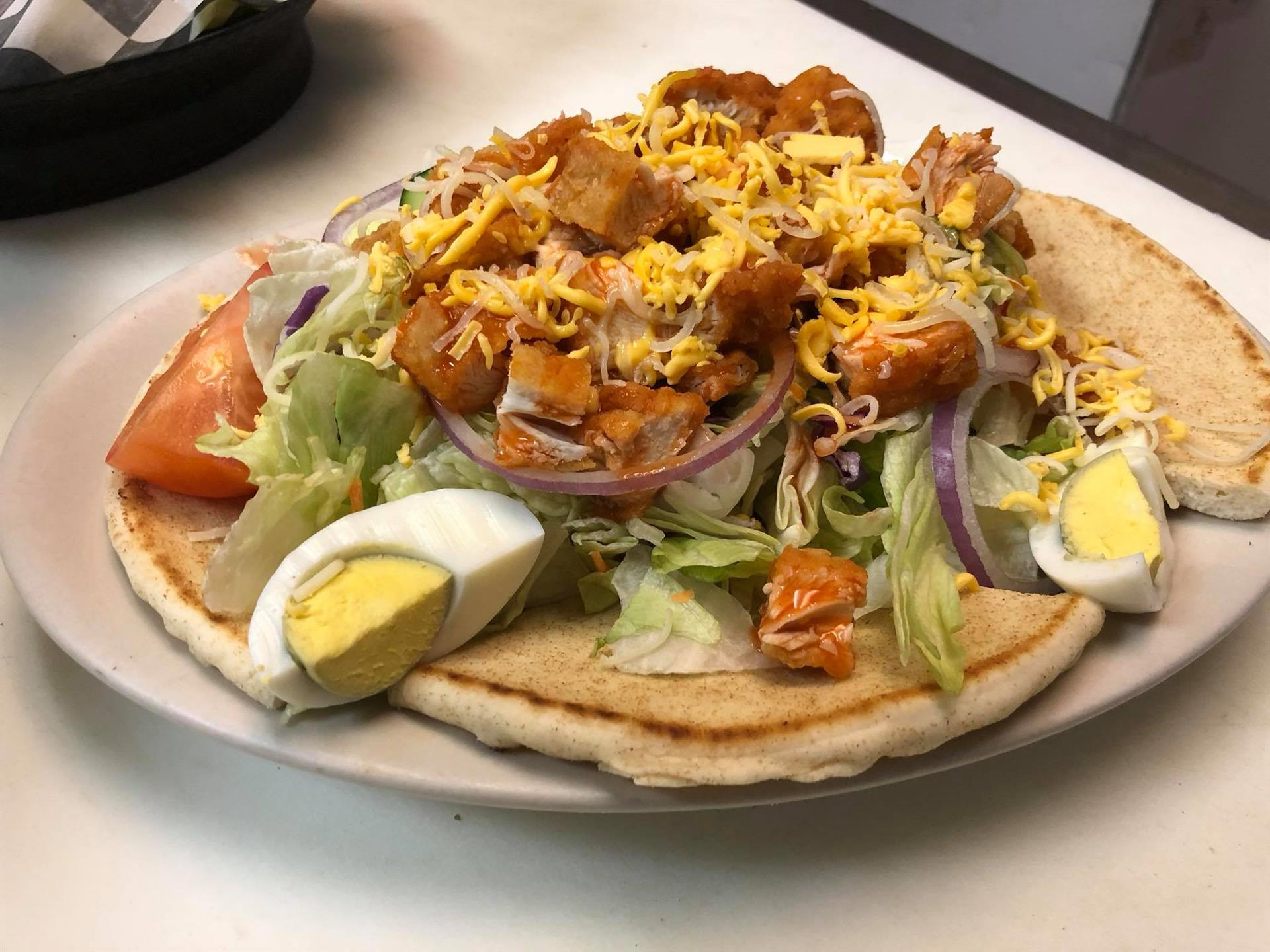 Buffalo chicken salad with cheese, onions and a hard boiled egg over pita