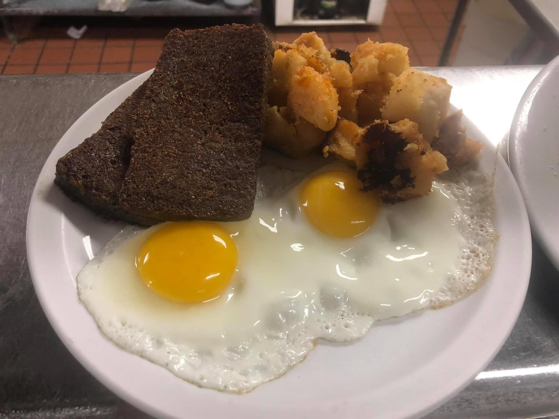 Two fried eggs with breakfast potatoes and sticky bun