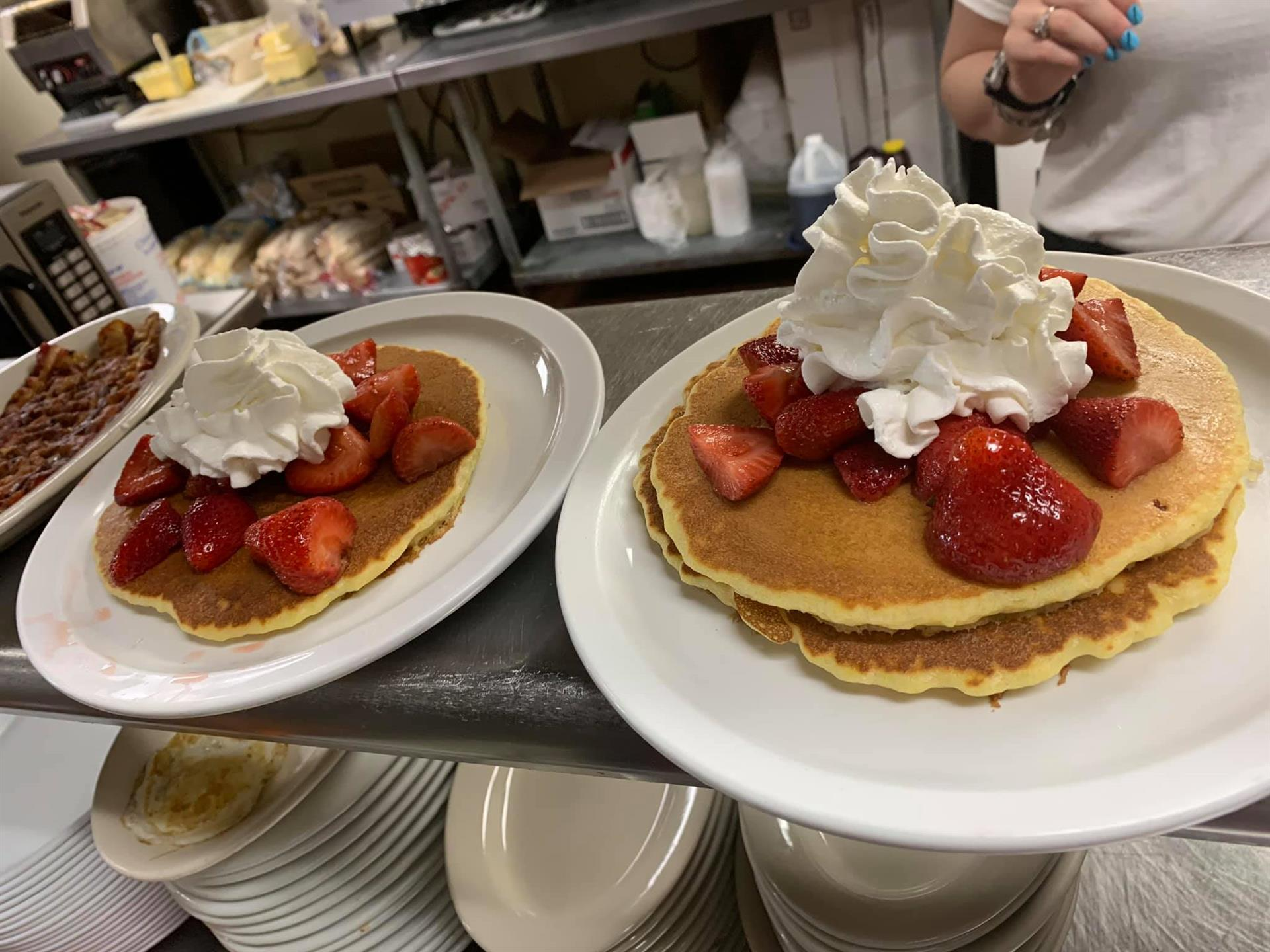 Pancakes topped with whipped cream and strawberries