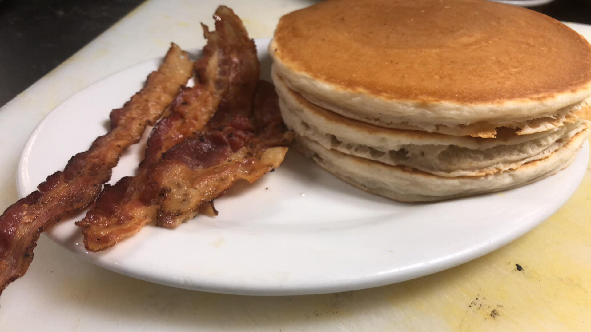 Stack of pancakes with a side of bacon