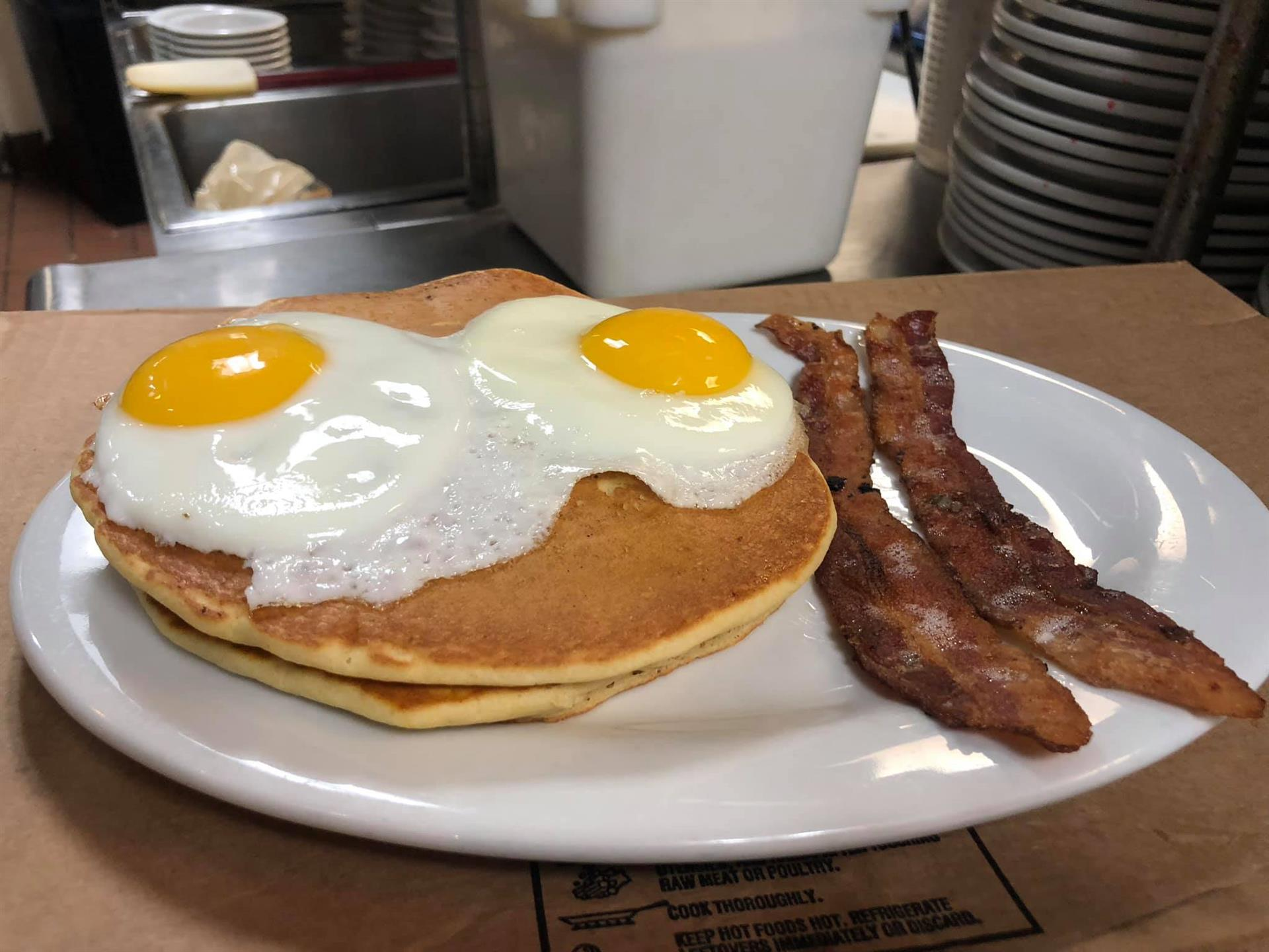 Stack of Pancakes with two sunnyside eggs with a side of bacon