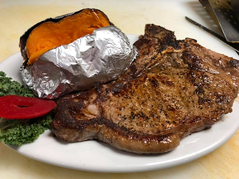 Steak with a baked sweet potato with garnish on the side