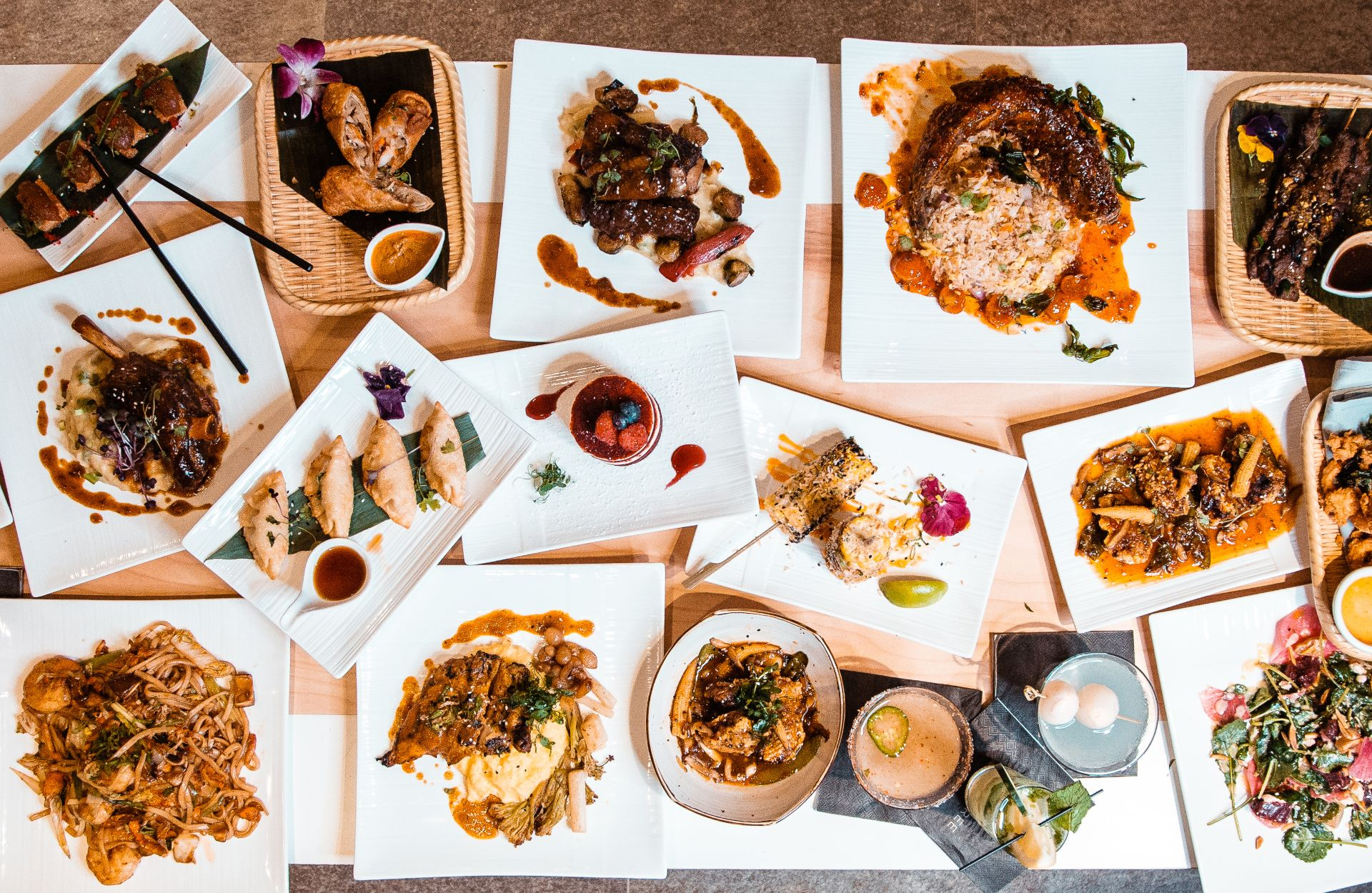 An assortment of Asian inspired entrees, appetizers and desserts on plates