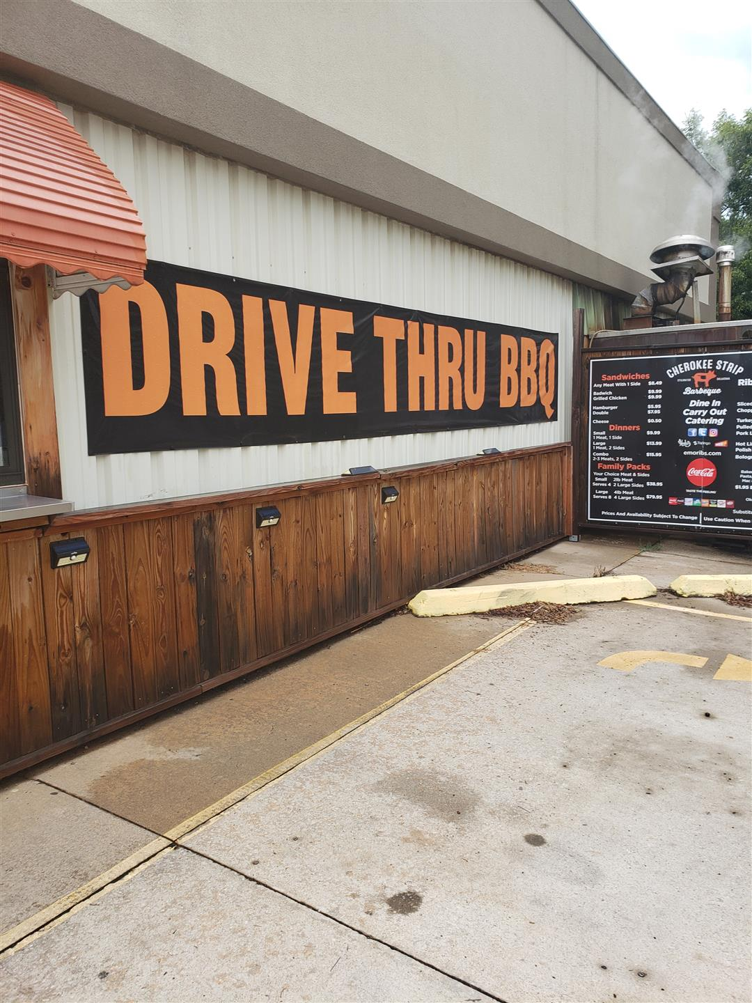 "exterior building signage that says 'drive thru bbq"" along with the drive thru menu for cars to see"