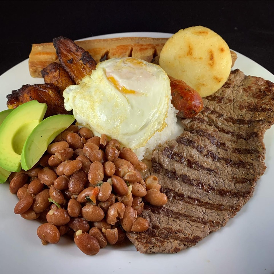 Grilled skirt steak with beans, a fried egg, sliced avocado and plantains