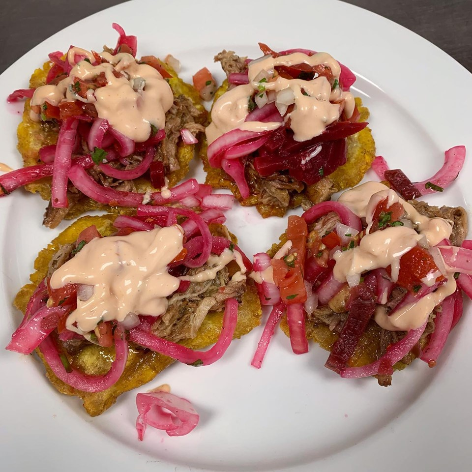 Fried plantain topped with pulled pork and pickled red onions topped with a sauce