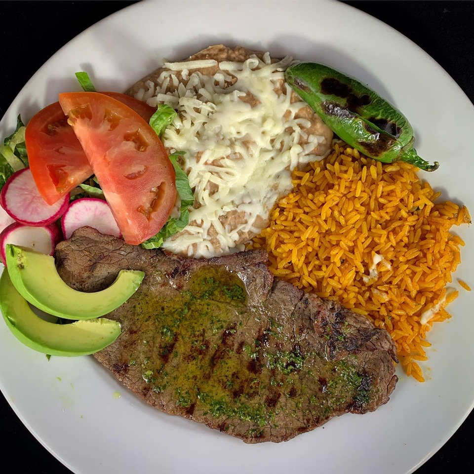 Grilled skirt steak with a bed of rice, sliced avocado, sliced tomato, green chili pepper, and refried beans topped with cheese