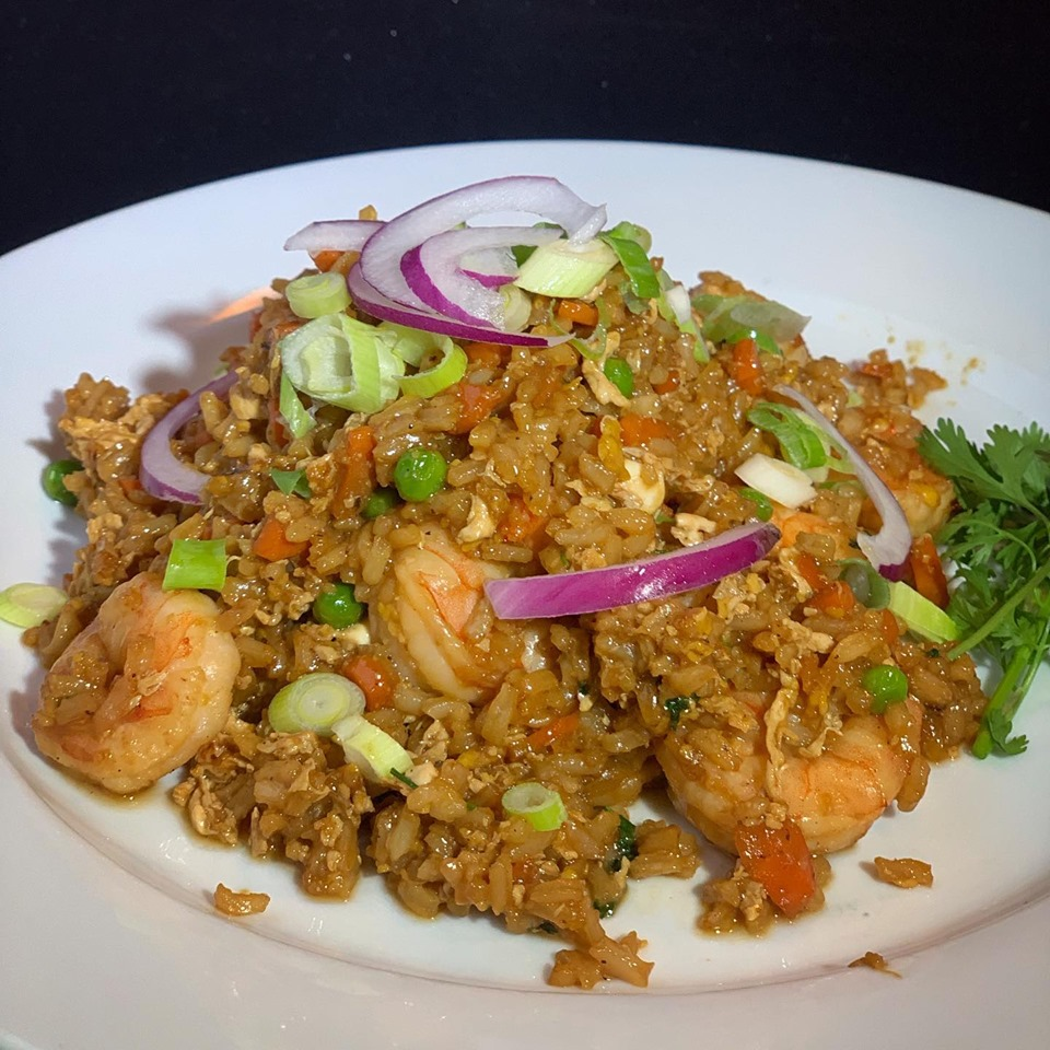 Fried rice with grilled shrimp topped with red onions and green onions with fresh parsley on the side