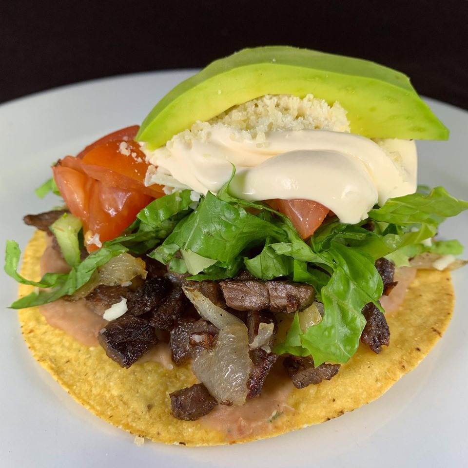 Fried plantain tortilla topped with meat, lettuce, tomoato, sliced avocado, mayo and parmesan cheese