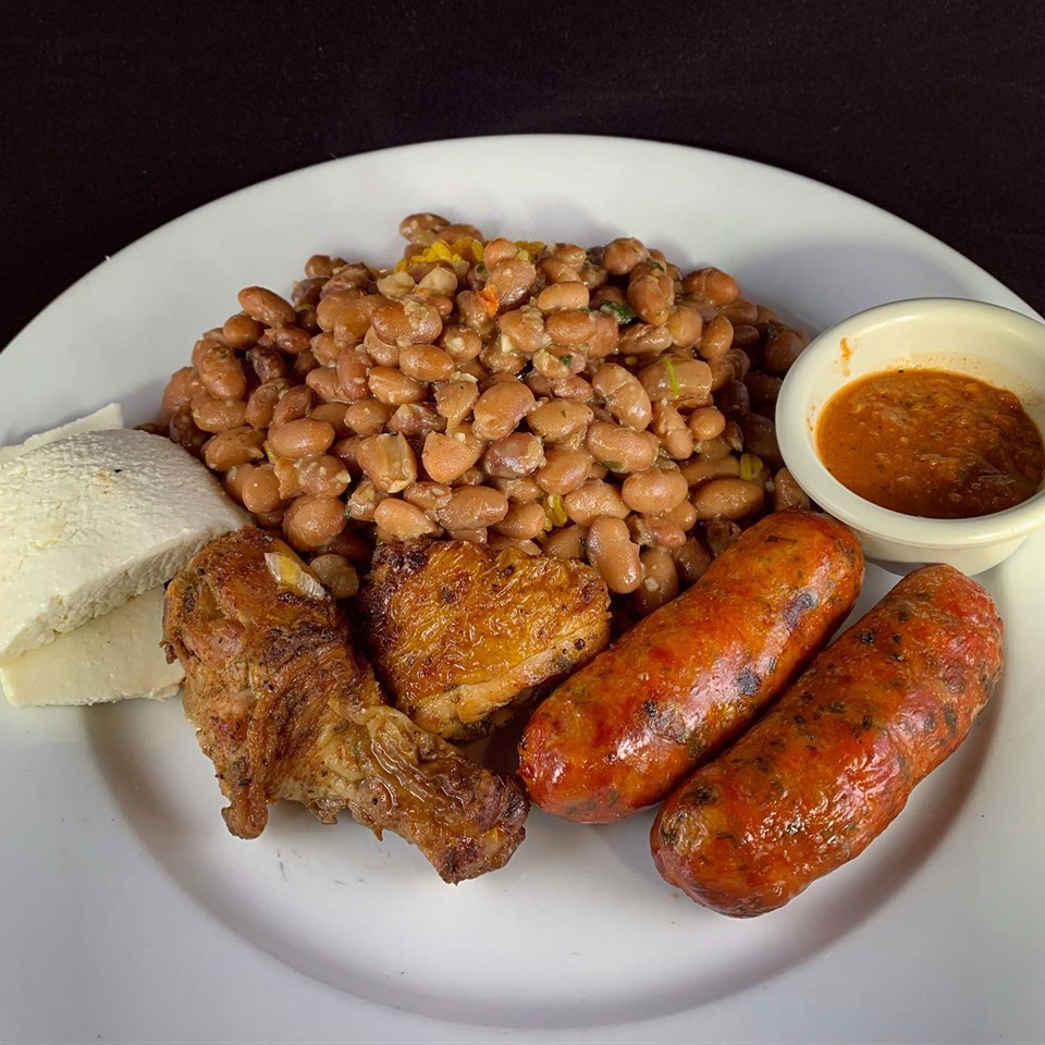 chicken wings, sausage links, and refried beans with a side of pita bread and curry sauce
