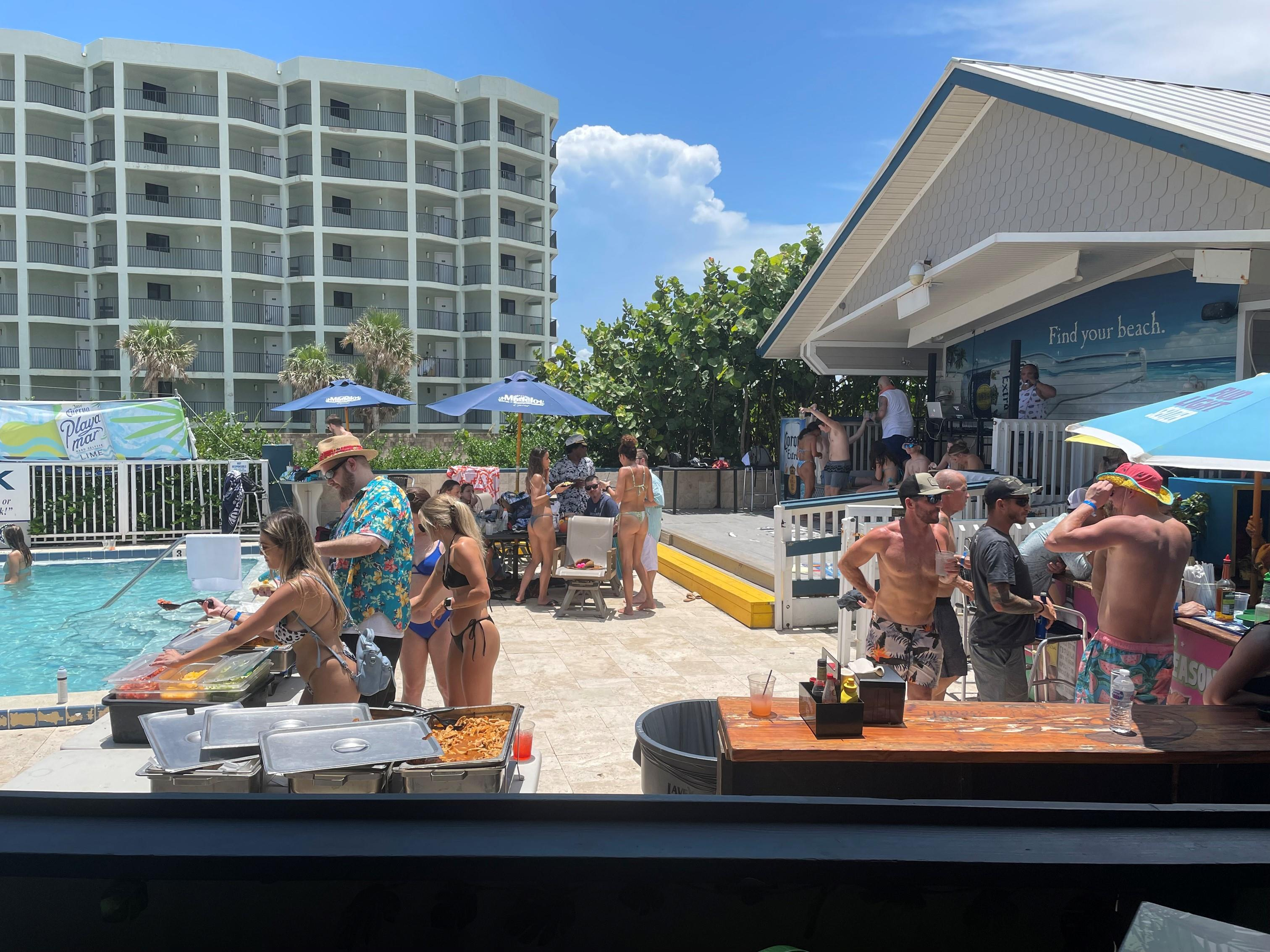 people bbqing by a pool