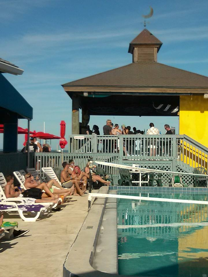 outdoor pool area with customers relaxing on beach chairs