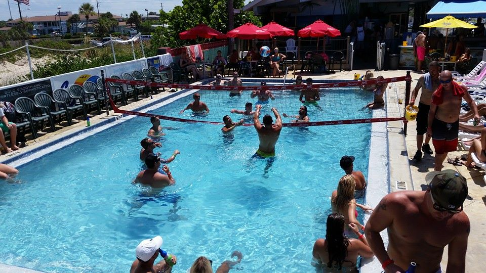 large pool party with a group of people playing volleyball in the pool
