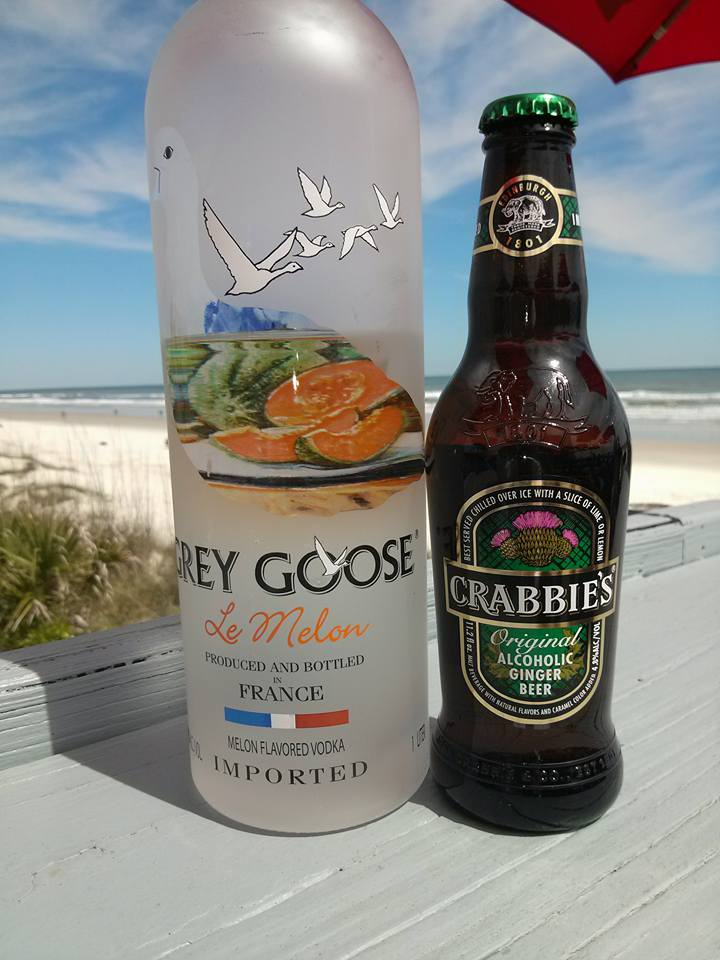 a bottle of grey goose and a bottle of crabbie's ginger beer on a counter overlooking the beach