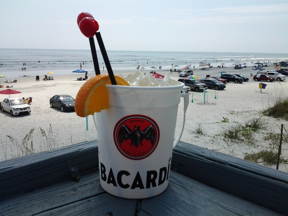 mixed bacardi drink on a counter overlooking the beach parking lot