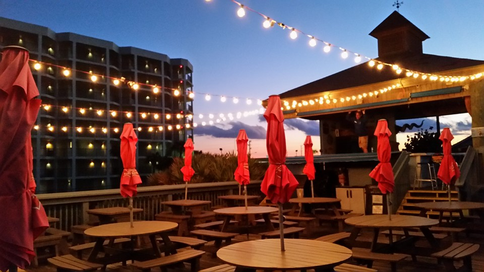 outdoor patio with tables, chairs, umbrellas and string lights