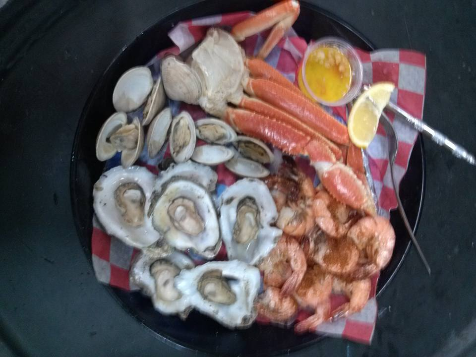 basket of clams, oysters, shrimp and crab legs with butter sauce