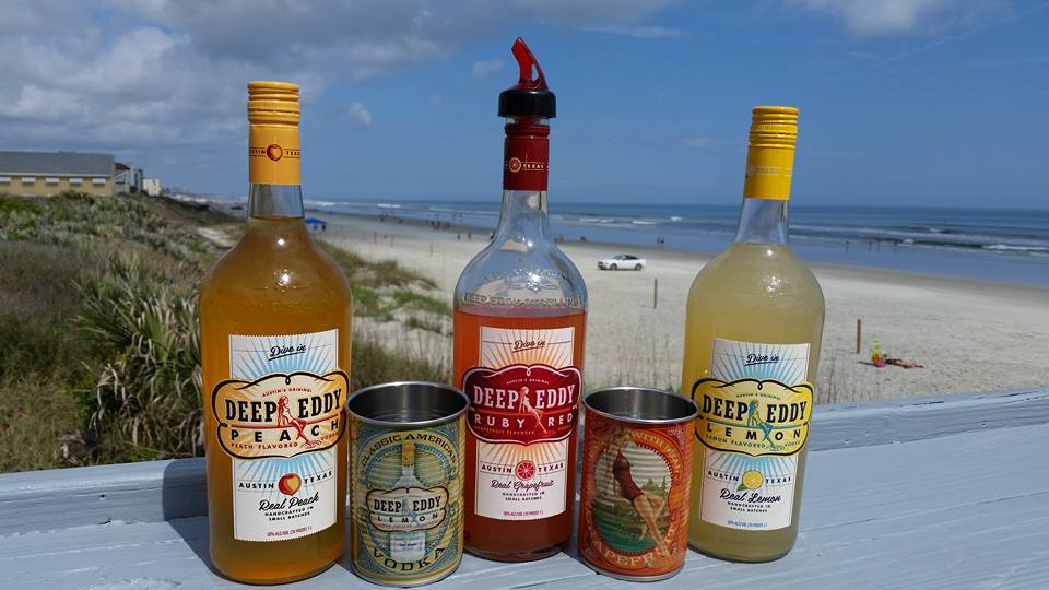 three different bottles of deep eddy with tin cans being displayed on a counter overlooking the beach
