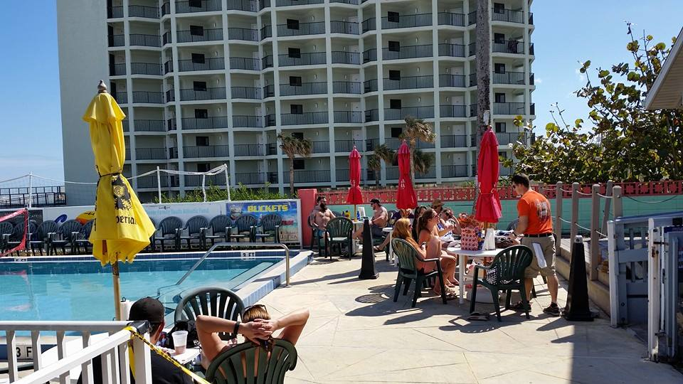 outdoor patio next to the pool with customers, tables and chairs