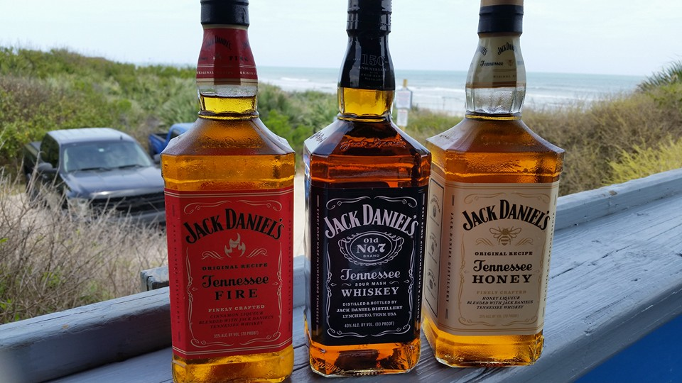 three different bottles of jack daniels being displayed on a counter overlooking the beach