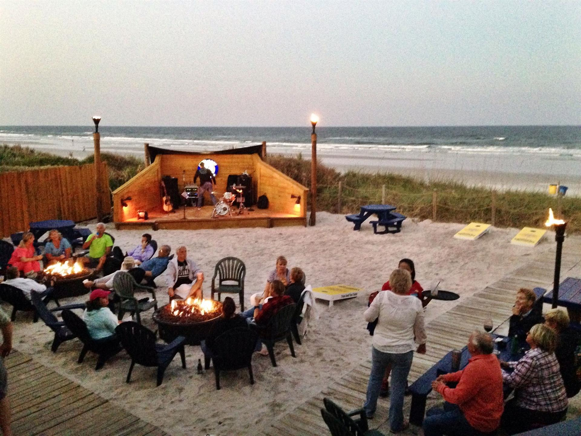 outdoor sand pit with small campfires, chairs and an area for a live band