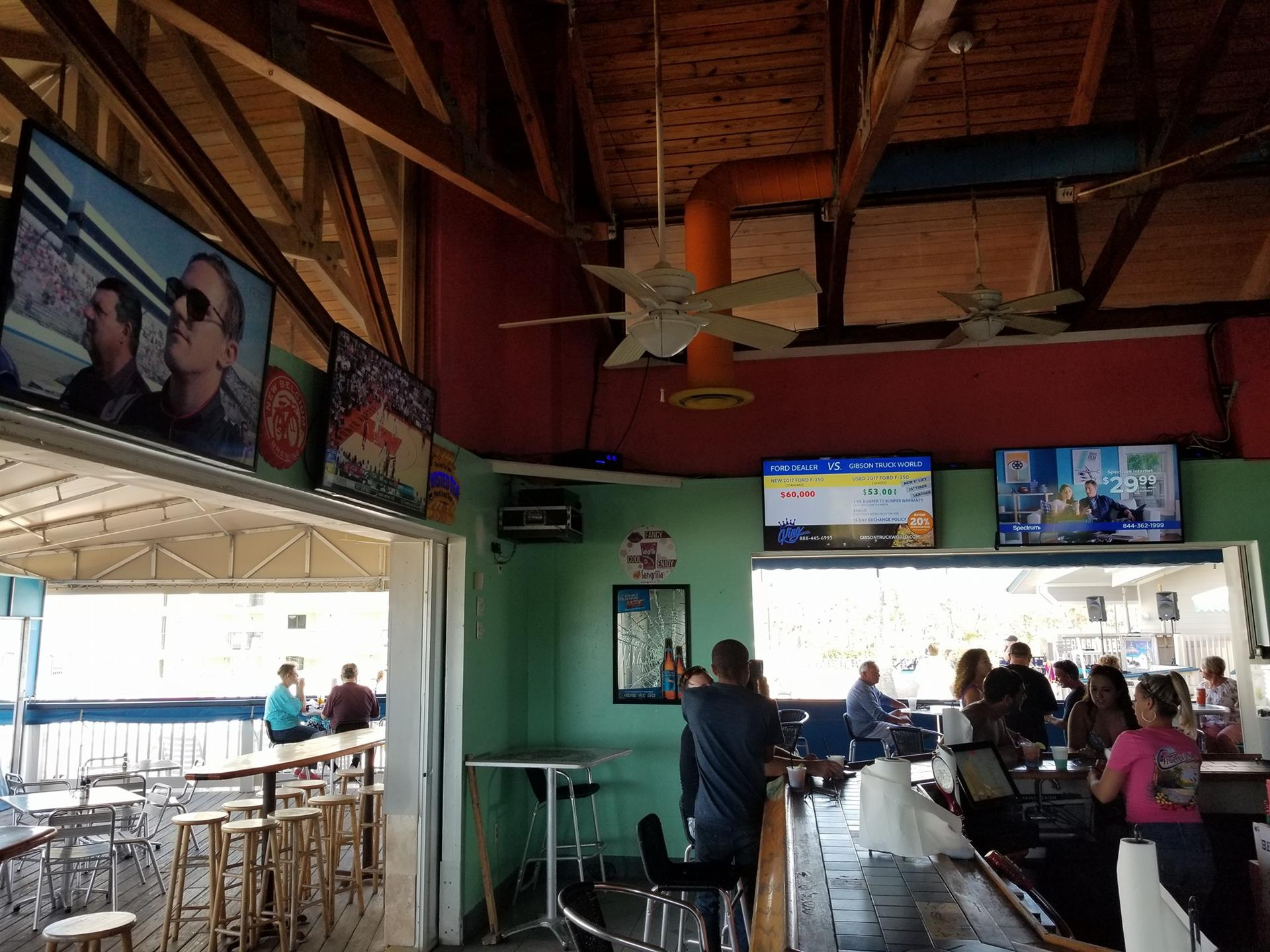 interior bar with tvs on the wall with customers crowded around the counter