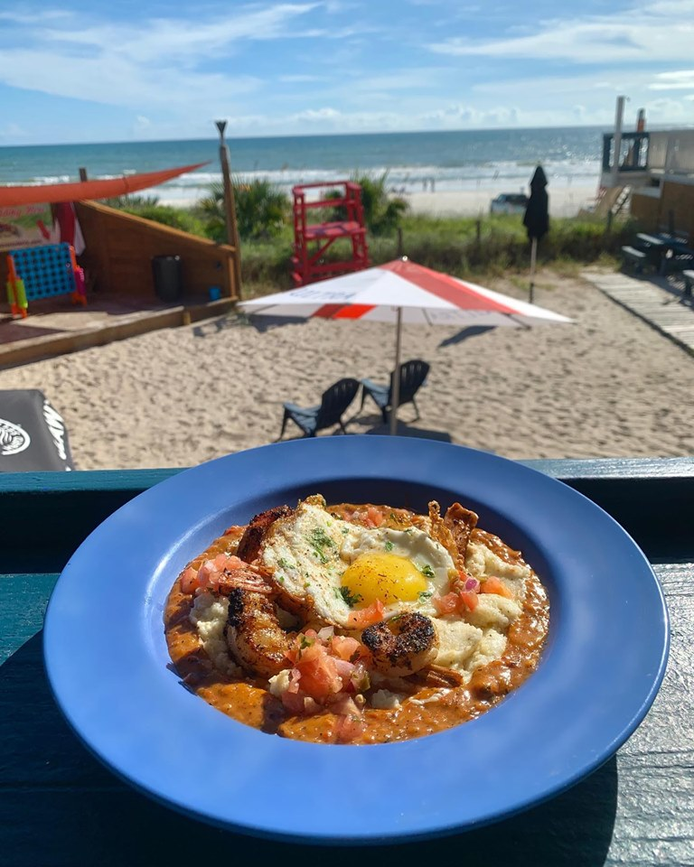seafood gumbo with a fried egg on a counter overlooking the beach and outdoor sand area