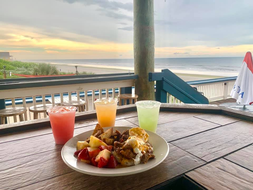 brunch plate with eggs and fruit on the table by the beach with sunset in the back