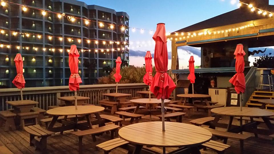 tables set up with string lights and umbrellas on the outdoor dining deck