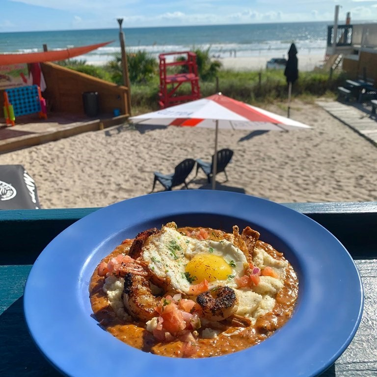 shrimp and grits with a fried egg on the back patio with view of the beach