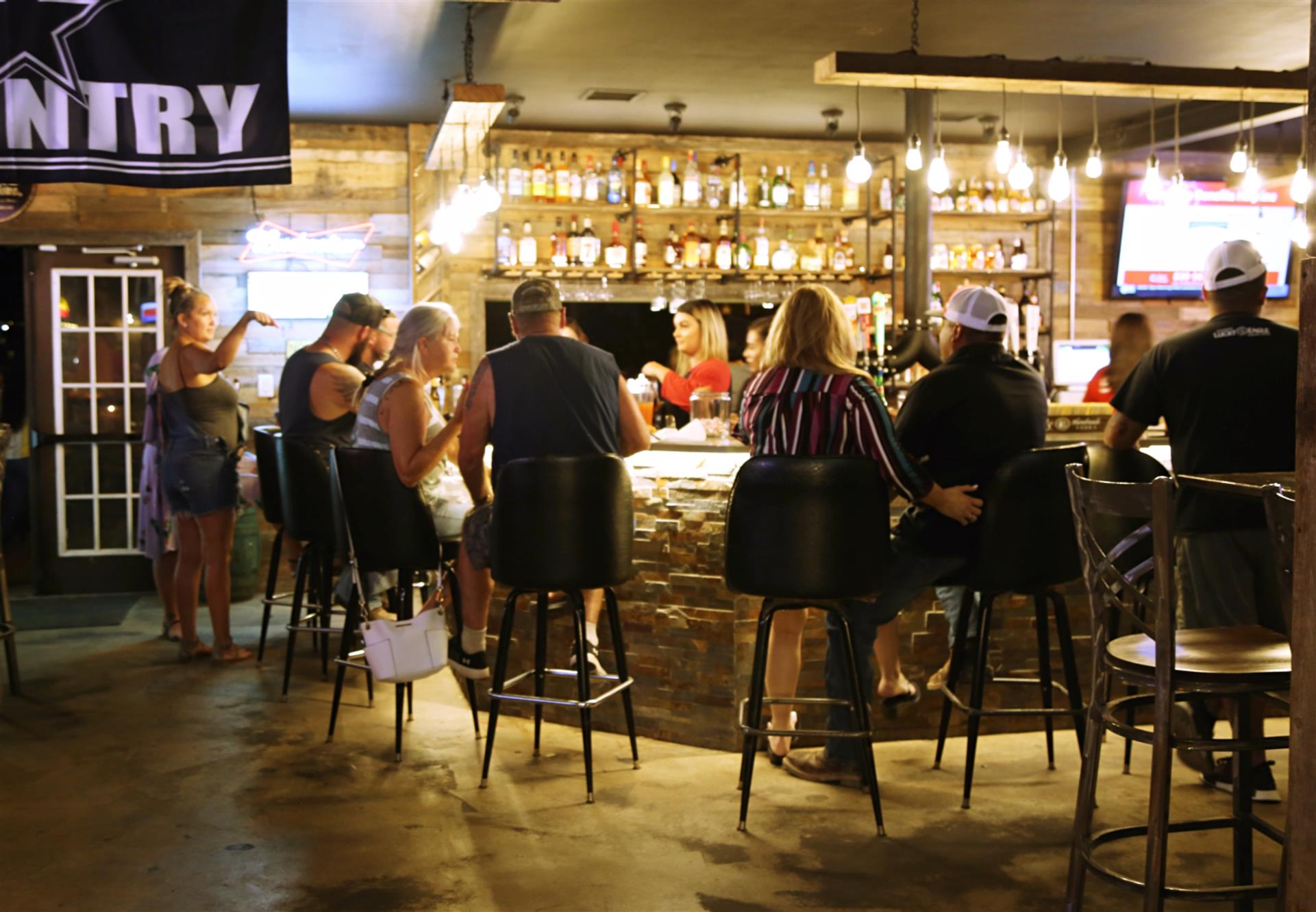 interior bar with customers crowded around the counter sitting on stools