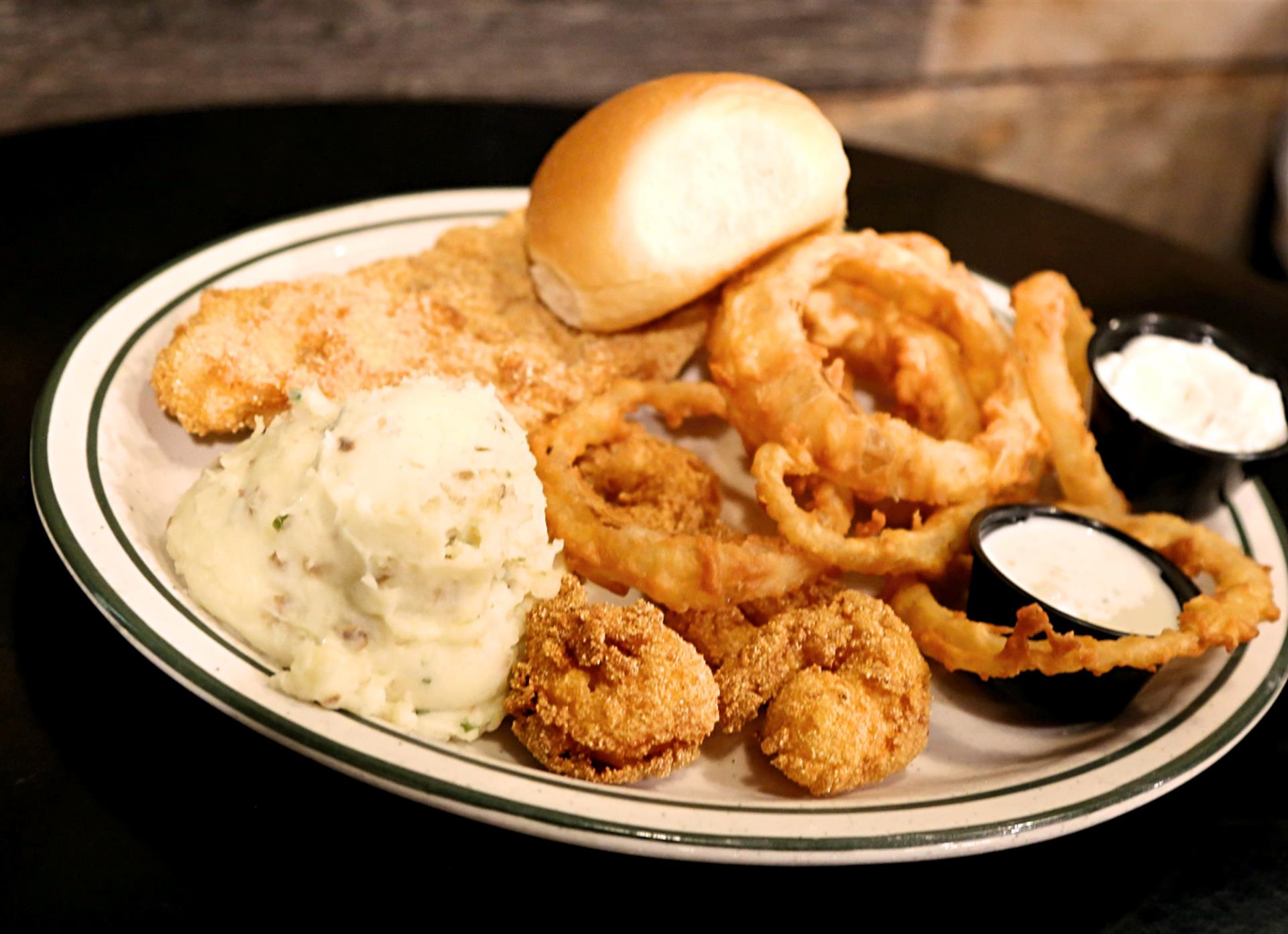 fried fish fillet with a side of mashed potatoes, fried shrimp, onion rings and a roll