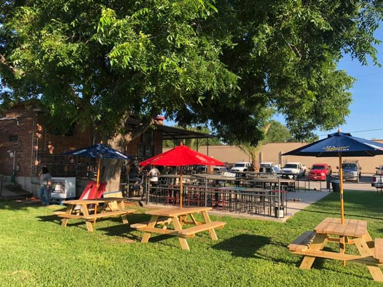 outside area with picnic tables and umbrellas setup