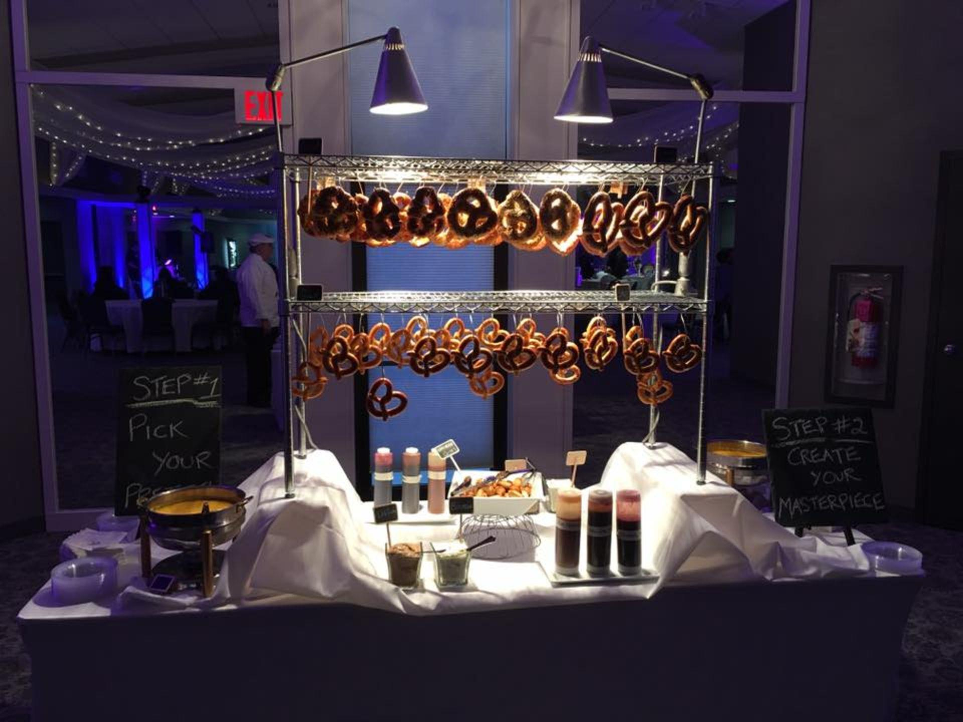 Pretzels hanging from a metal rack on a table with an assortment of toppings