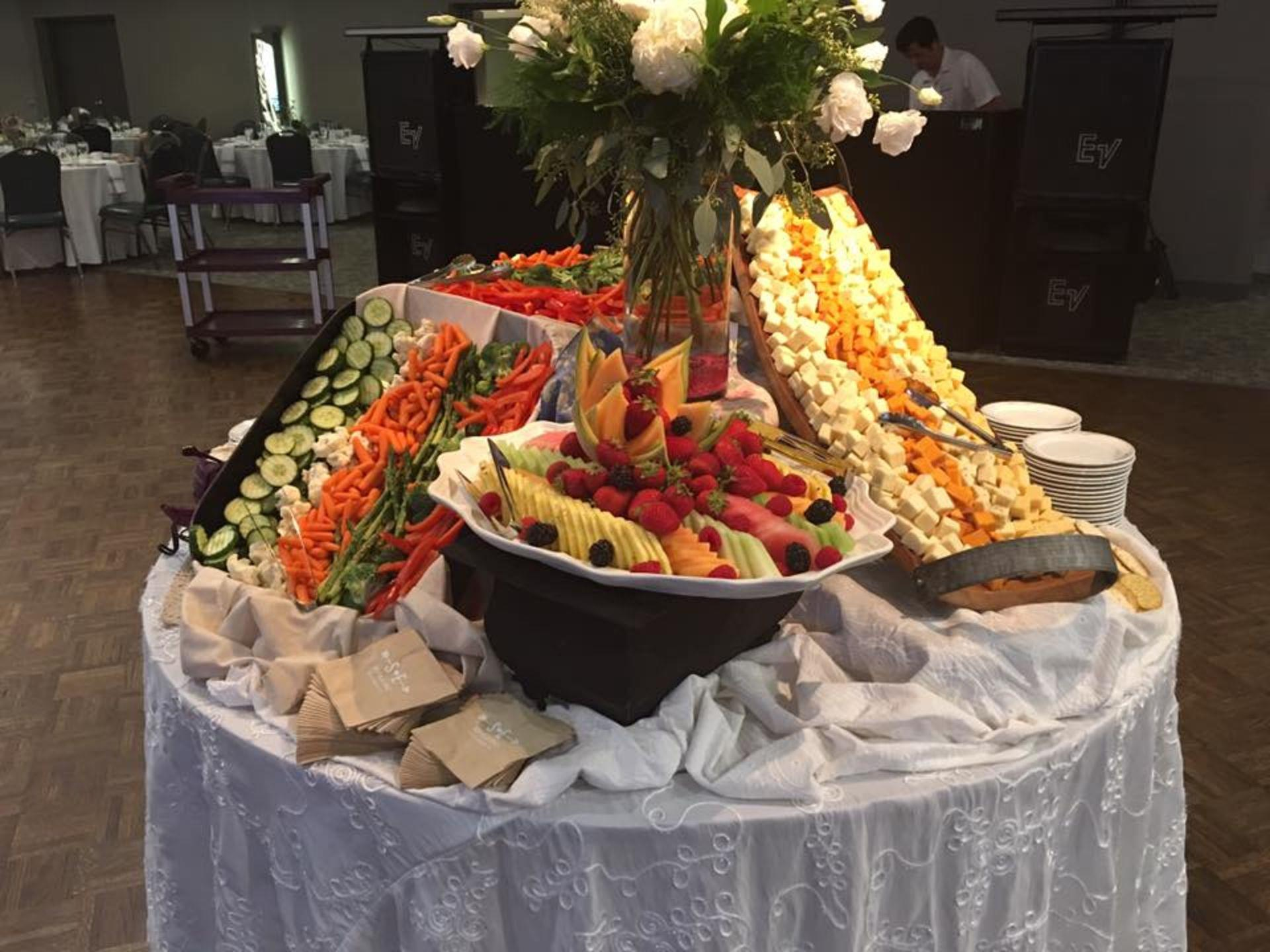 Assorted fruits, vegetables and cheeses on a display table