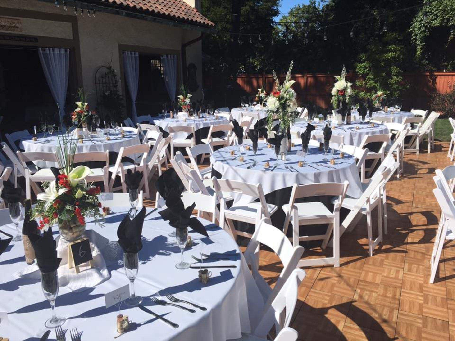 Outdoor dining setting for a wedding with tables set with flowers, napkins, glasses and utensils